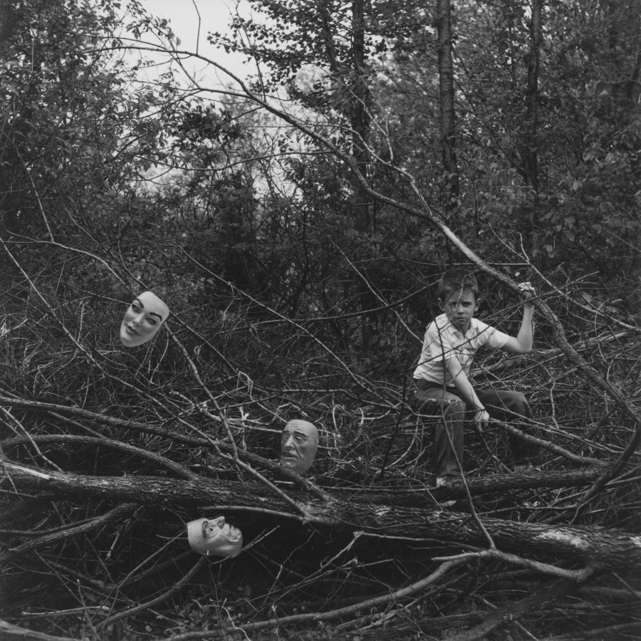Black-and-white photograph of a boy seated among felled tree branches containing three masks scattered within them