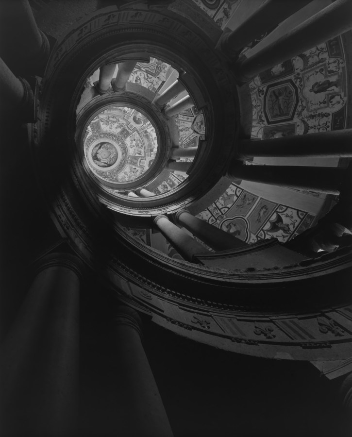 A black and white photograph of the view looking upward, at an elaborate spiral staircase.