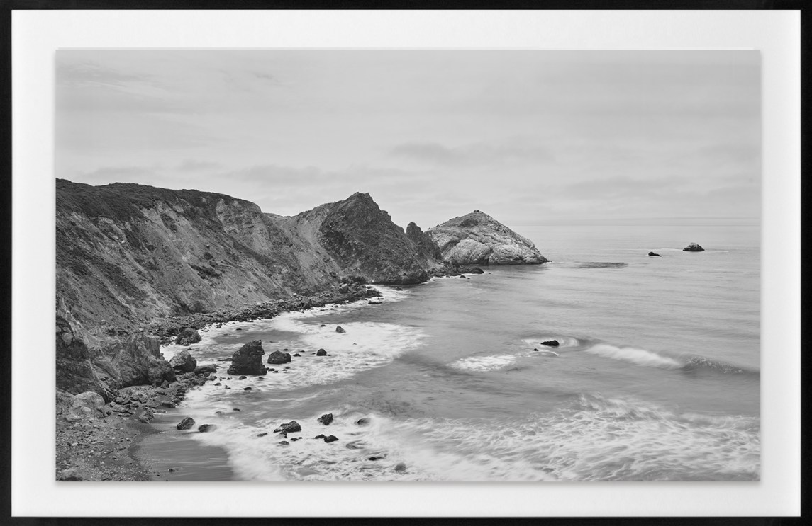 Black-and-white horizontal photograph of cliffs at the shoreline of the Pacific Ocean.
