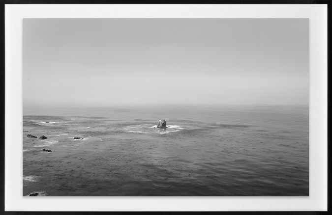 Black-and-white horizontal photograph of a lone rock in the Pacific Ocean.