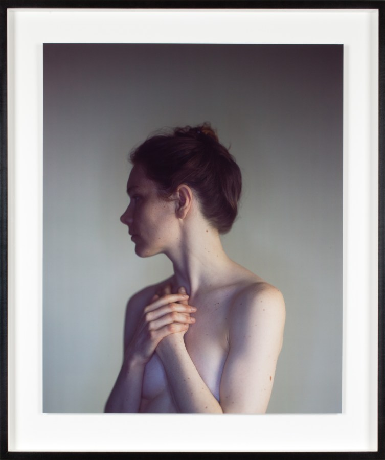 Color photograph of a nude white woman, arms clasped over her torso, looking away from the camera.