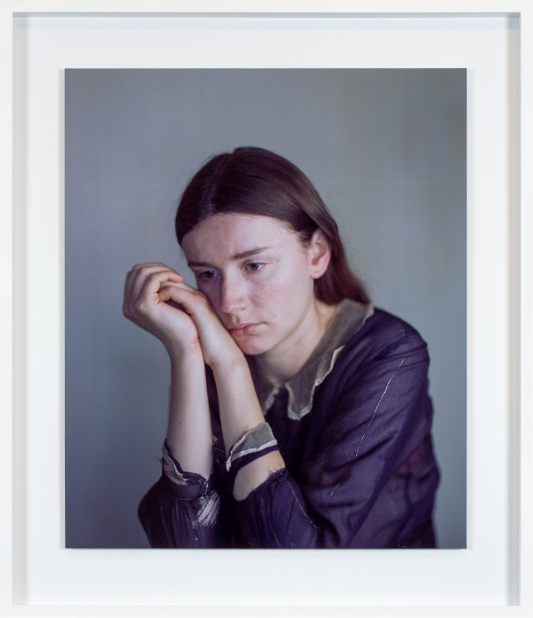 Color photographic portrait of a young woman in a purple shirt with her cheek resting on her clasped hands