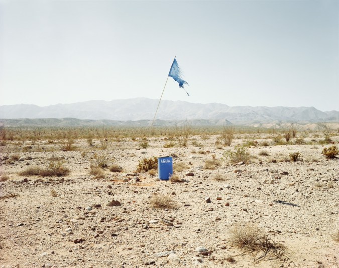 Color photograph of a tattered blue flag standing next to a blue barrel marked AGUA in a desert landscape