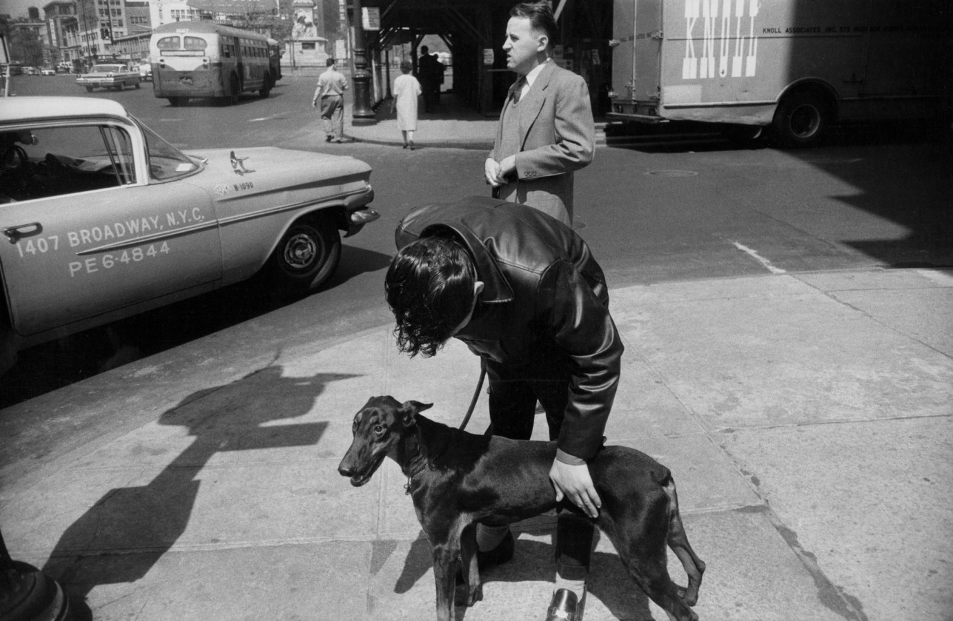 Black and white photograph of two men on the street, one leaning over a medium-sized black dog