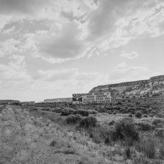 """Black-and-white photograph of a New Mexico landscape, with a billboard that reads """"Bring Your Cameras"""""""