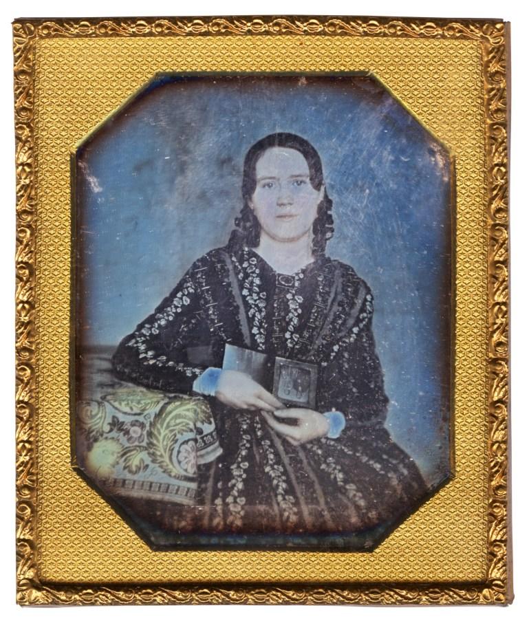 Cased daguerreotype portrait of a white woman holding a daguerreotype.
