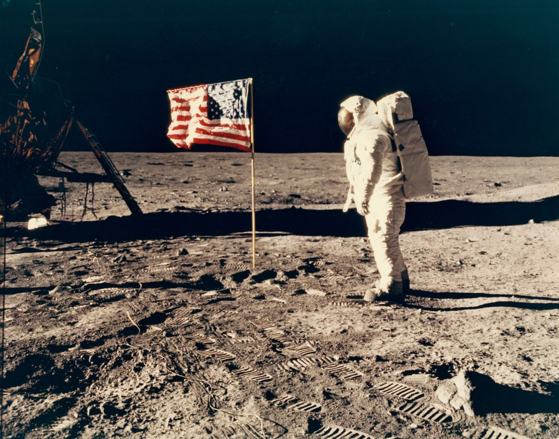 Color photograph of an astronaut and American flag on the moon