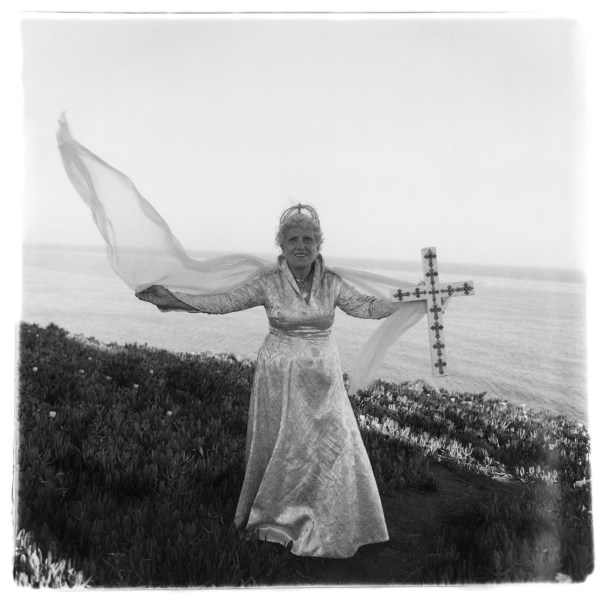 Black-and-white photograph of a woman in a white dress holding a cross, her veil blows in the wind