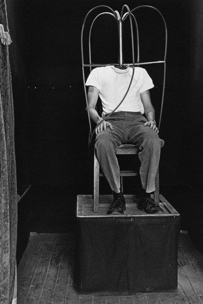 Black-and-white photograph of a headless man sitting on a chair on top of a pedestal