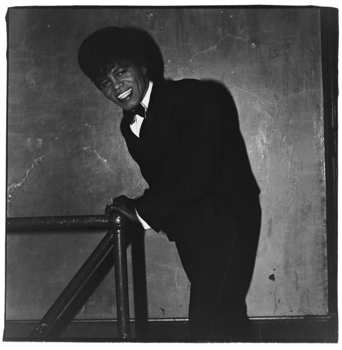 Black-and-white photograph of James Brown leaning against a post