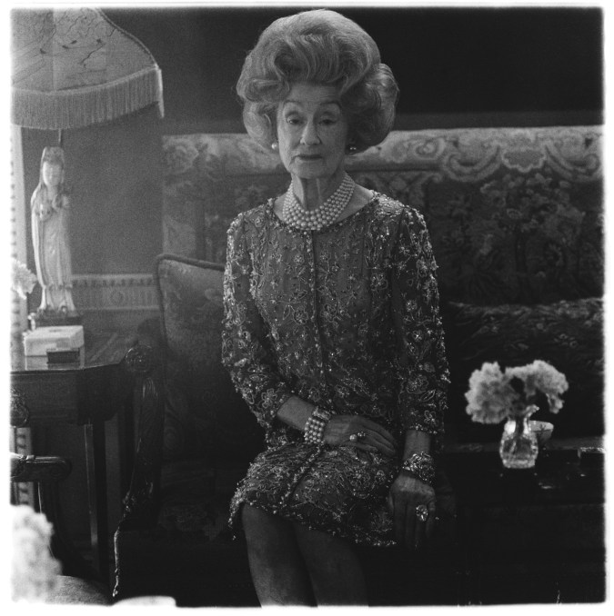 Black-and-white photograph of a woman sitting in an ornate room