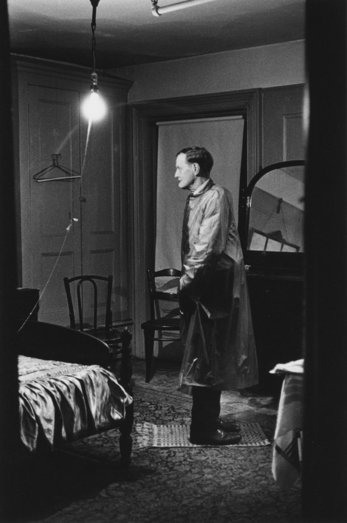 Black-and-white photograph of a man with his head facing the opposite way of his body in a room lit by a single lightbulb