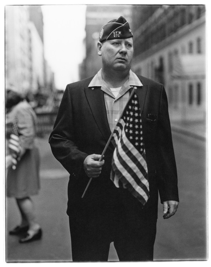 Black-and-white photograph of a man standing in a street holding an American flag