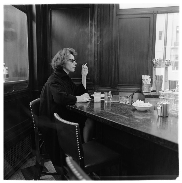 Black-and-white photograph of a woman sitting alone at a counter