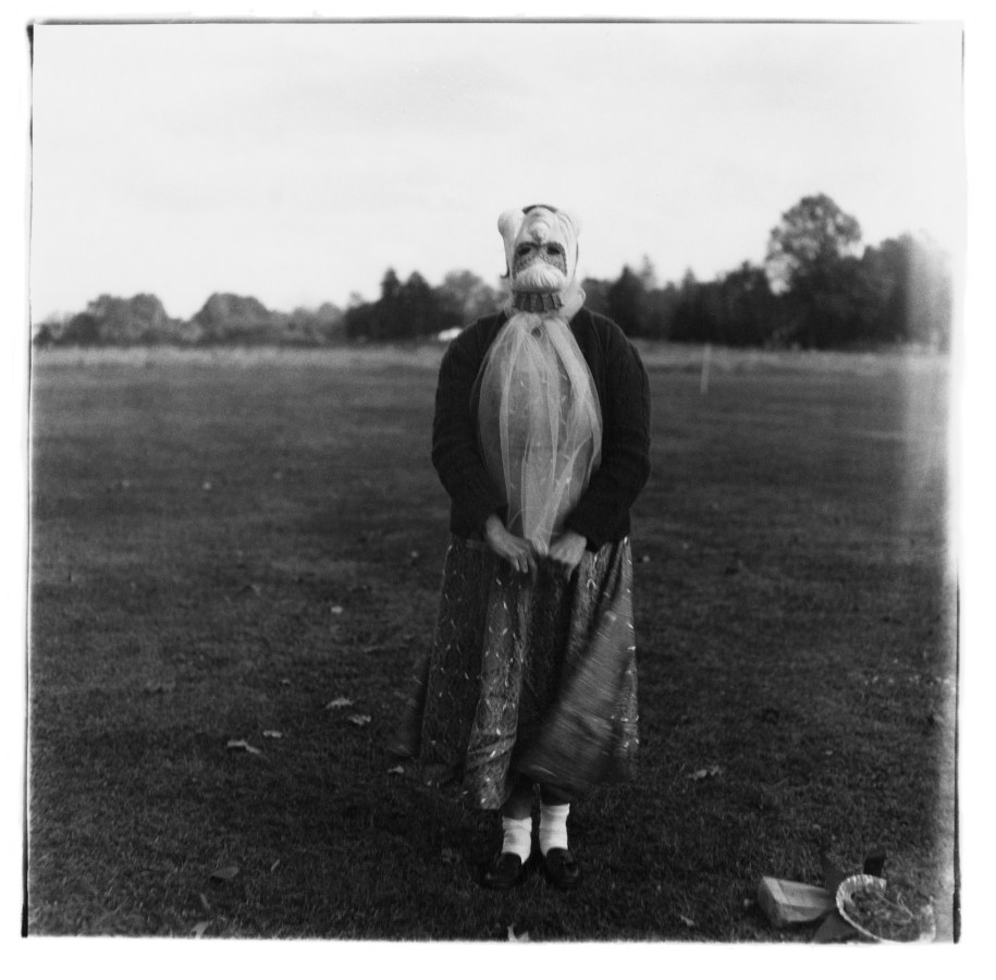 Black-and-white photograph of a figure wearing a mask with a field in the background