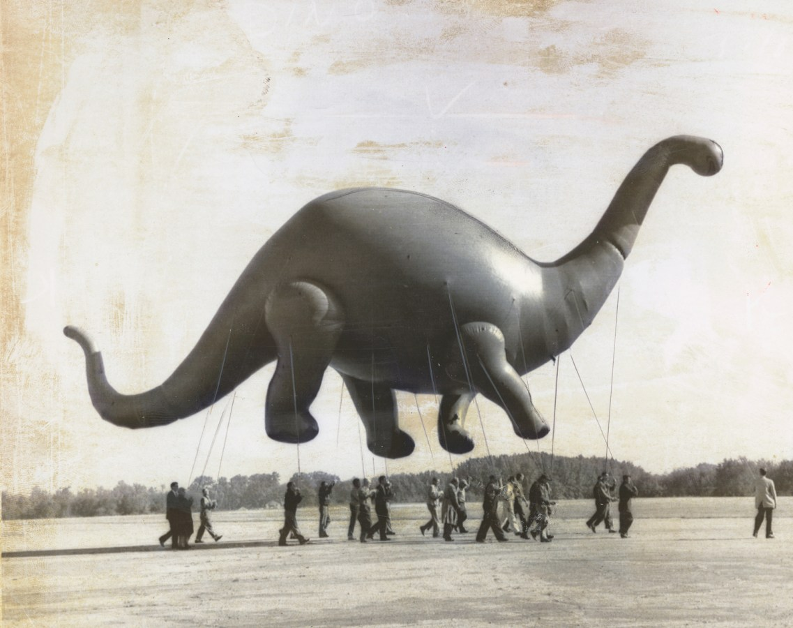 Black-and-white horizontal photograph of a group walking with a parade-sized dinosaur balloon.