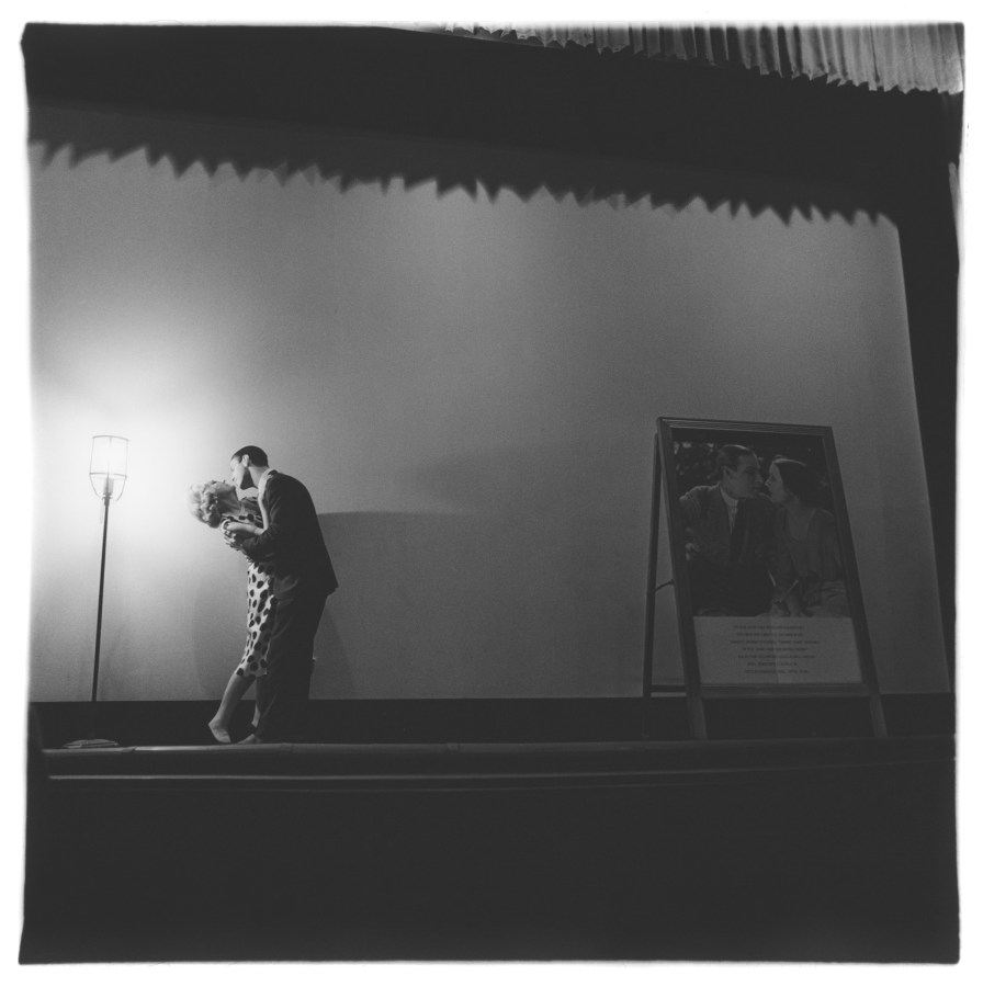 Black-and-white square photograph of two figures in embrace on an empty stage, the their left is a single floor lamp illuminating the scene to their right is a poster depicting a couple kissing