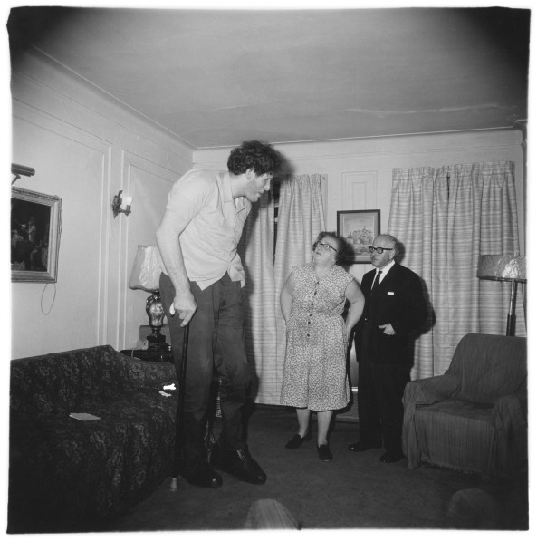 Black-and-white photograph of three figures standing in the center of a living room