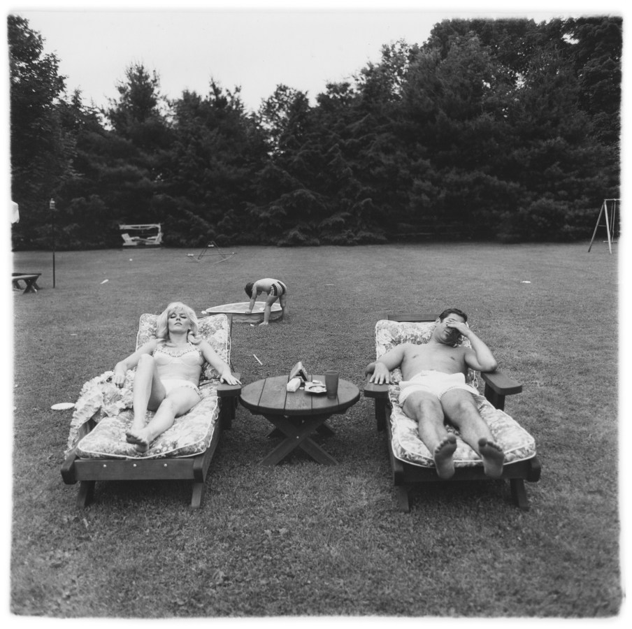 Black-and-white photograph of a man and woman laying in lounge chairs while a child plays in the background