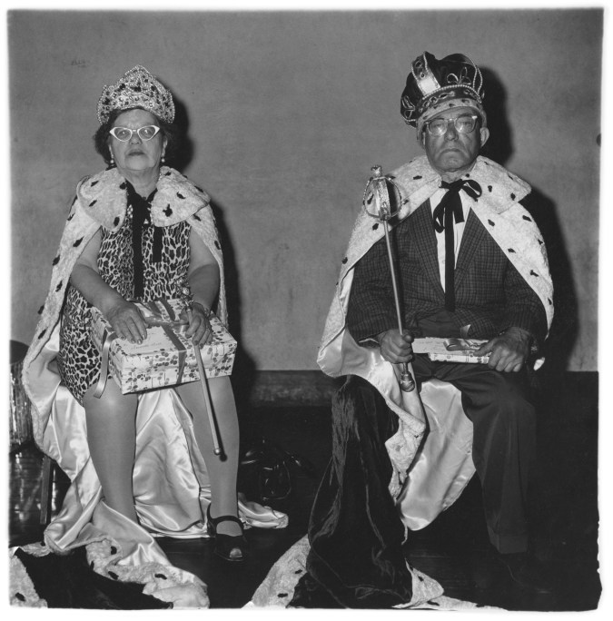 Black-and-white photograph of an elderly couple wearing king and queen costumes