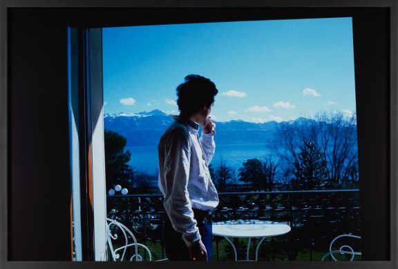 Color photograph of a man smoking a cigarette in an open double doorway to a balcony overlooking mountains on a lake