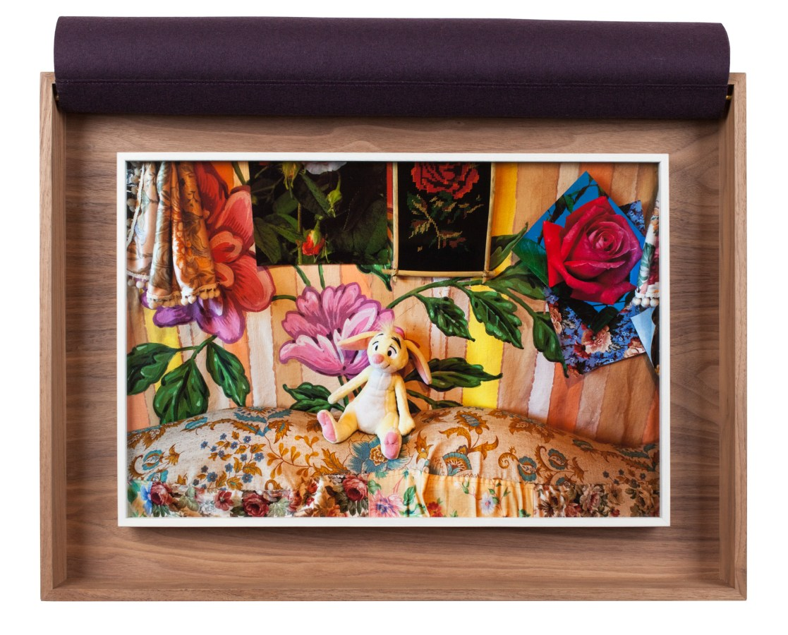 A framed photograph of a child's toy against brightly colored, flowered fabric, in a wooden box.