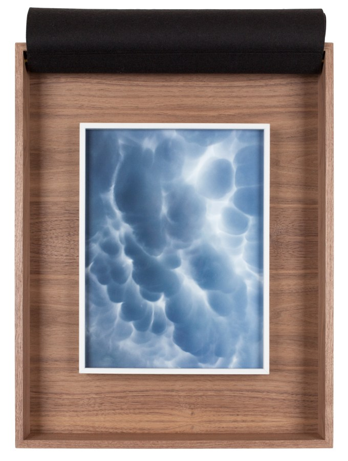 A framed photograph of clouds in the sky, inside a wooden box