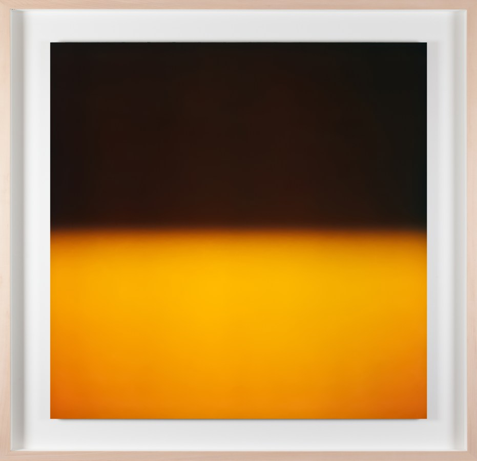 A framed photograph of a color field, black in the top half and bright yellow in the bottom half