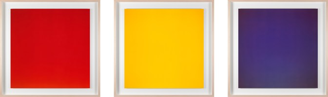 Triptych of three square photographs, one red, one yellow, and one blue