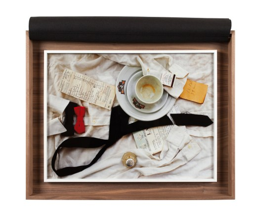 A box with a photograph of a waiter's uniform, with a cup and saucer, a pepper shaker, and checks on top