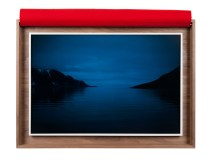 A framed photograph of a body of water, reflecting a dark blue sky, with small land masses on either side.