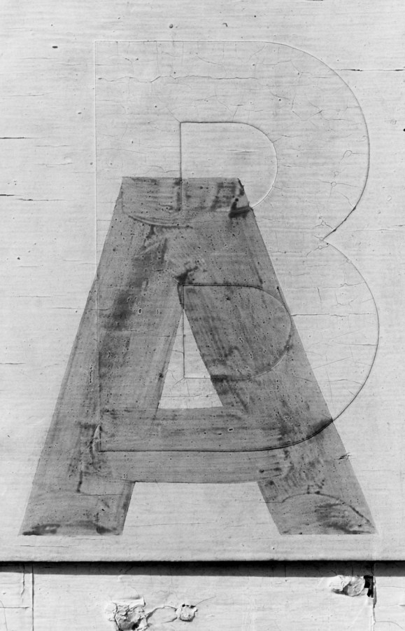 Black and white photograph of a detail of a hand painted sign of the letter 'A' painted onto a wall