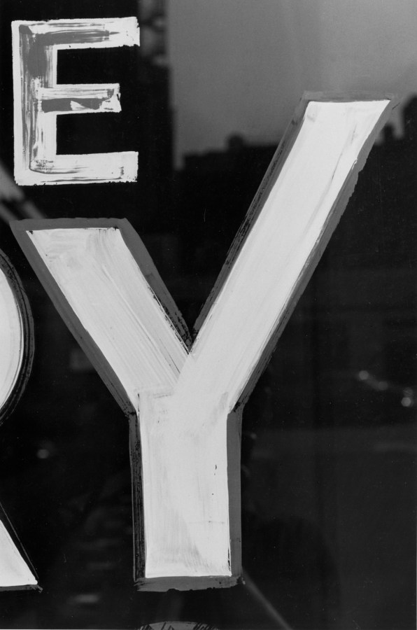 Black and white photograph of a detail of a hand painted sign