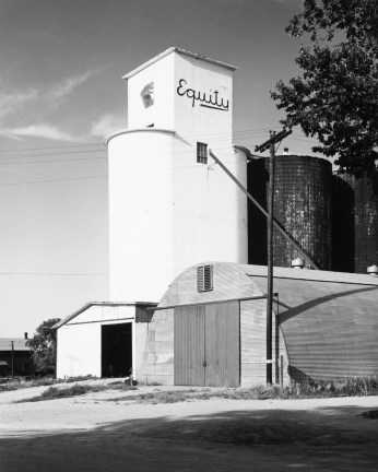 A vertical black and white photograph of a grain silo, with the word Equity painted at the top of the building