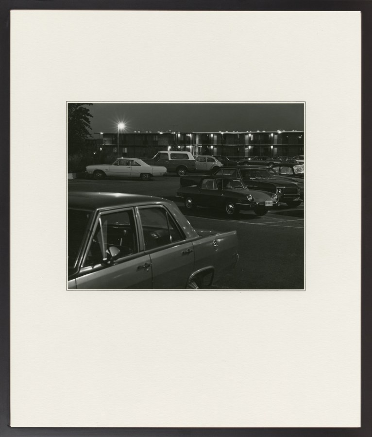 A framed black and white photograph of a parking lot at night, with 60s cars