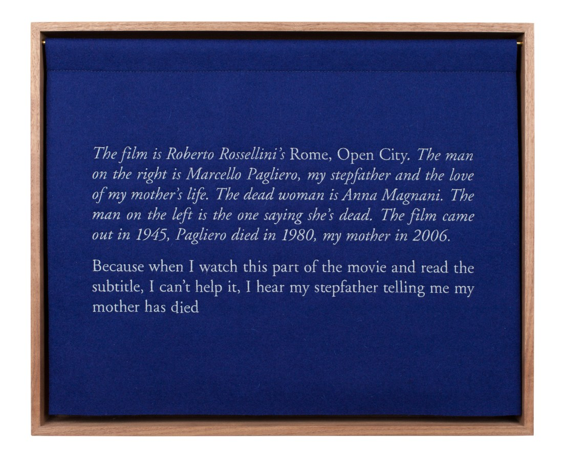 A wooden box with a blue curtian, embroidered with white text, describing the artist's stepfather