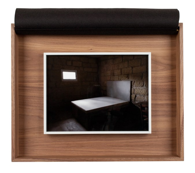 A framed photograph of a concrete bed, inside a wooden box