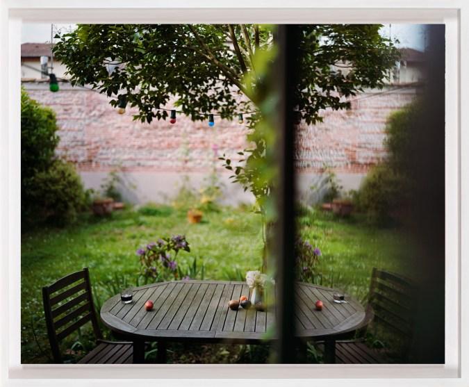 A framed photograph of a table in a garden, as seen through a window