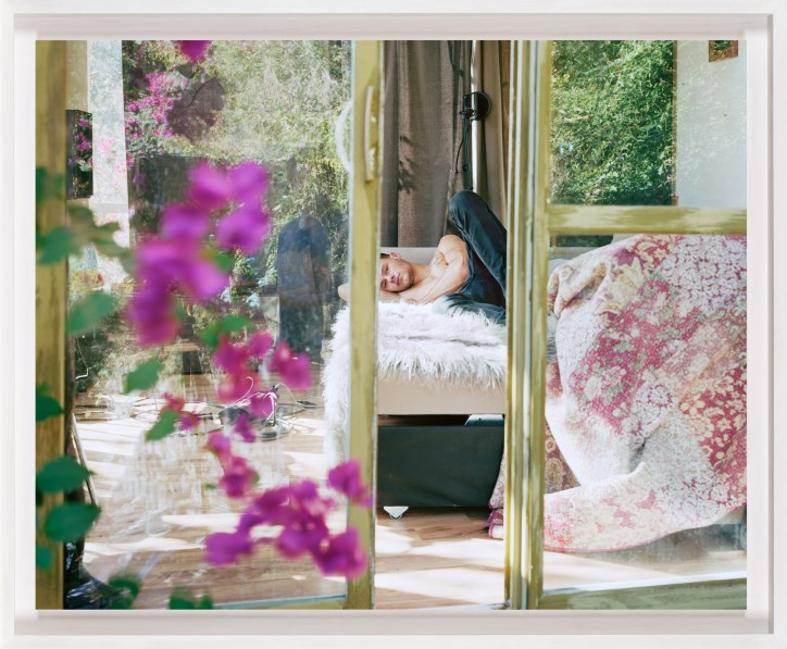 A framed photograph of a young man lying on a bed, as seen through a partially open sliding door. Pink flowers on the left