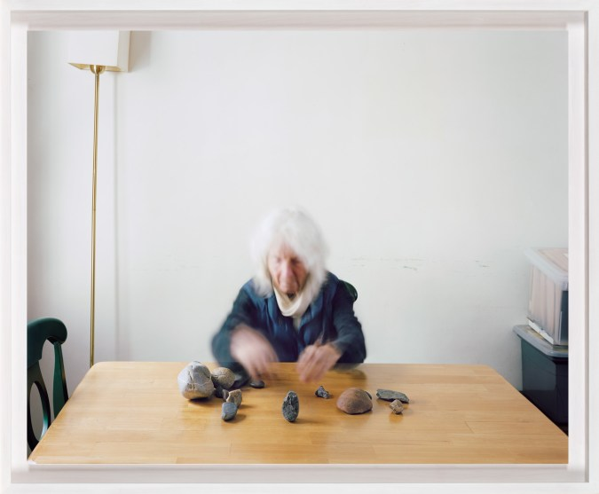 A framed photograph of a woman, blurred by movement, sitting at a table with a circle of small rocks in front of her