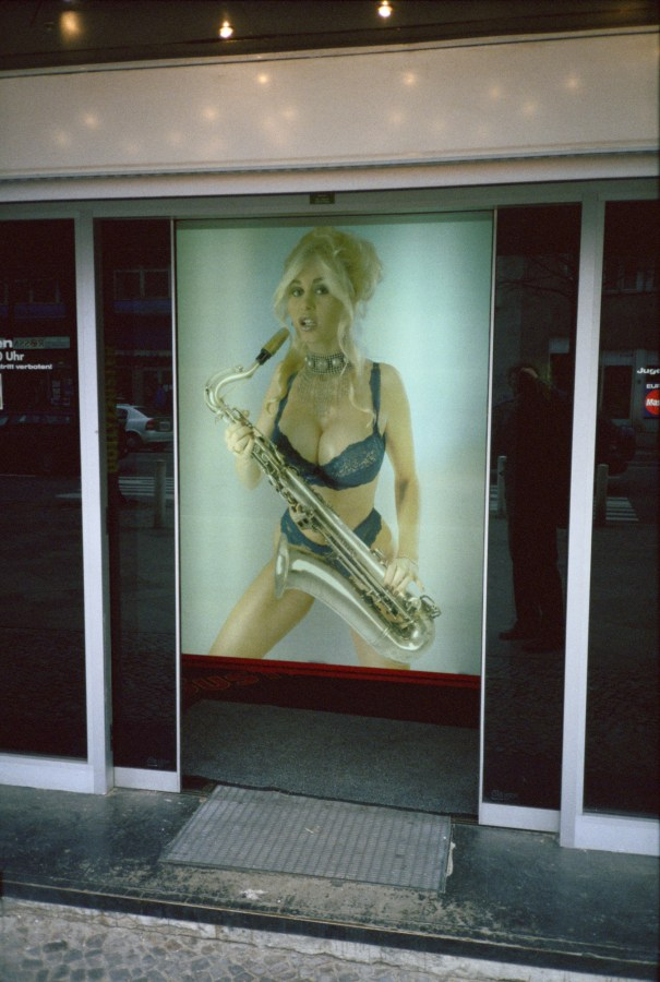 A photograph of an advertisement of a woman in lingerie playing a saxophone, behind sliding doors.