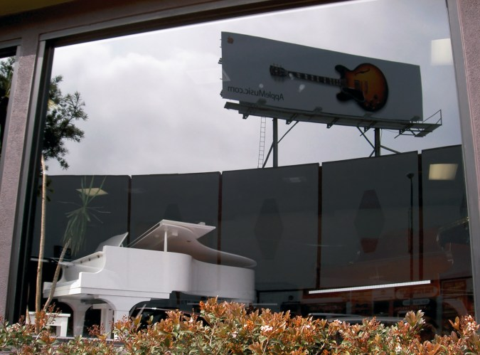 A photograph of a white grand piano seen through a window, upon which is reflected a billboard of a guitar.