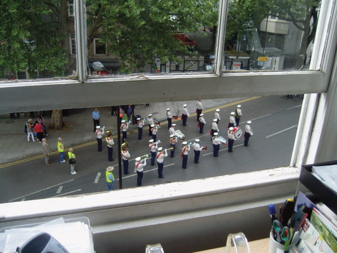 A photograph of a marching band, as seen through a barely-open window