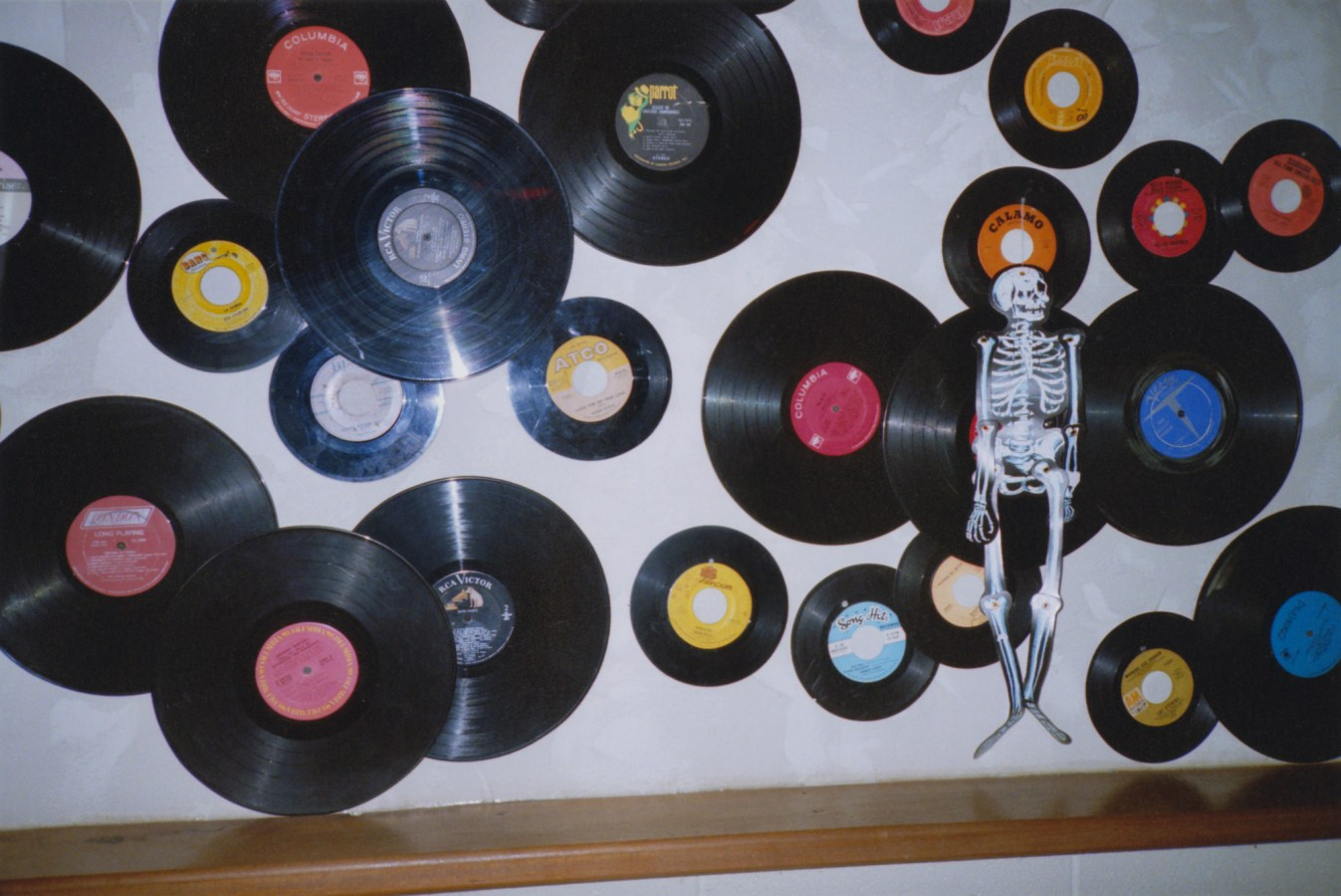 A color photograph of vinyl records mounted to a wall, along with a skeleton halloween decoration