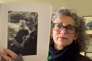 Video still of a person holding up an open book to a photograph of a woman seated in a garden