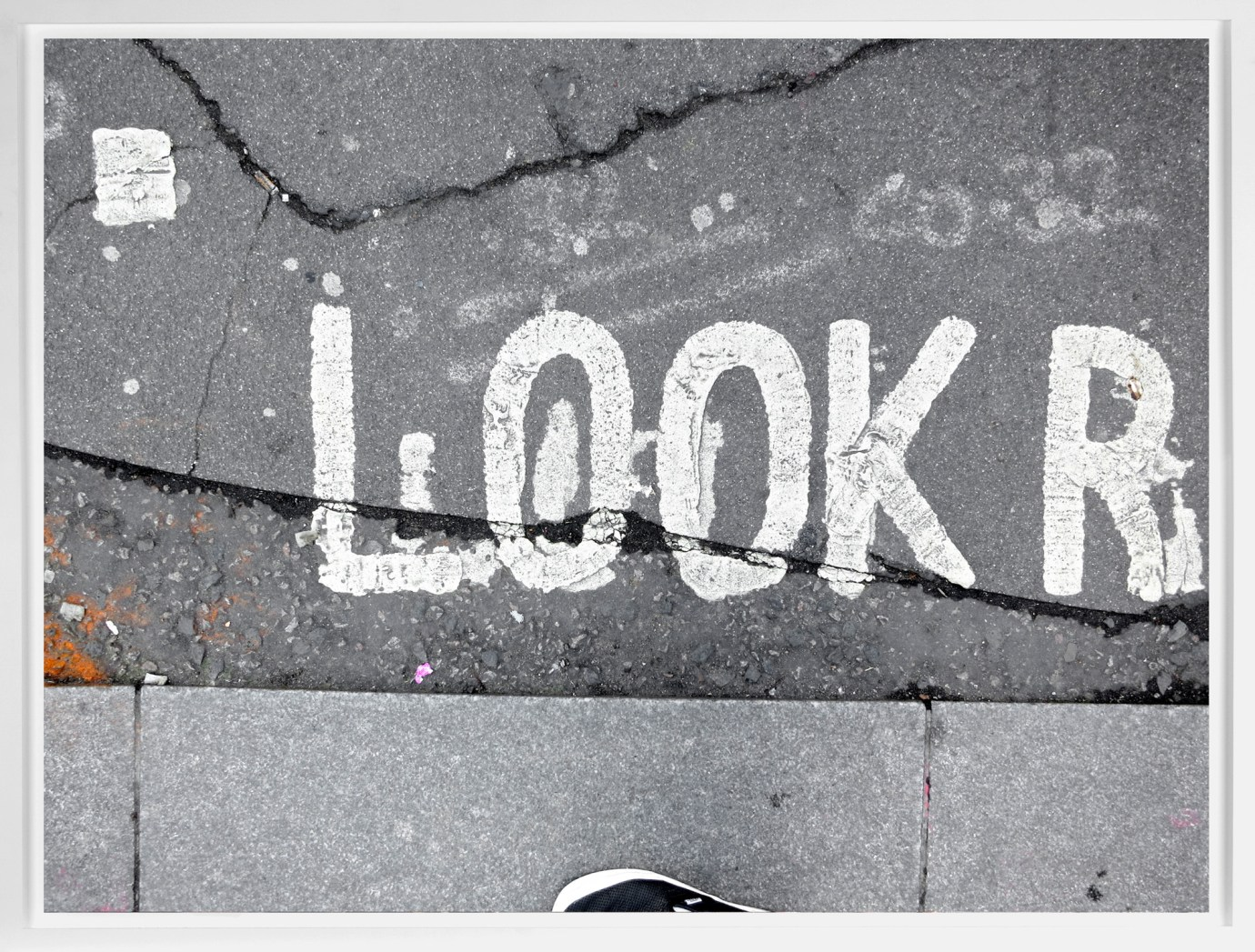 """A framed photograph of the word """"Look,"""" painted in the street near the sidewalk curb."""