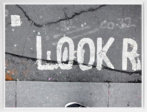 "A framed photograph of the word ""Look,"" painted in the street near the sidewalk curb."