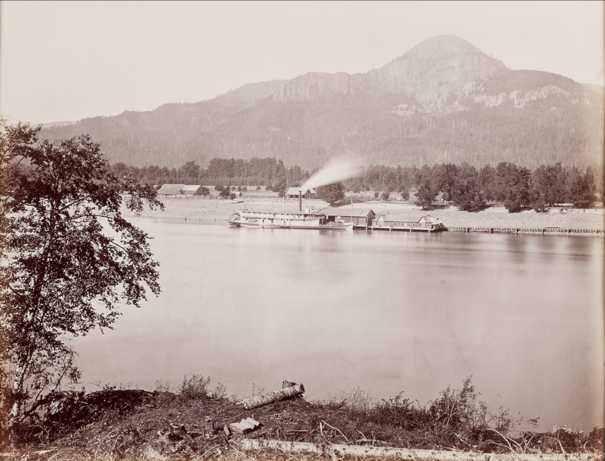 19th century photograph of a steam ship at a pier on a river with a mountain in the background