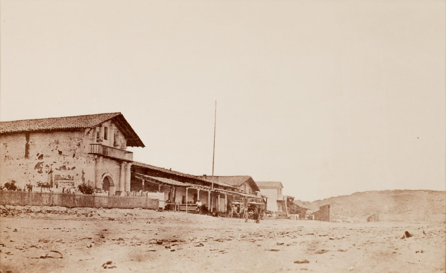19th century photograph of a cluster of buildings receding diagonally towards a hill in the background