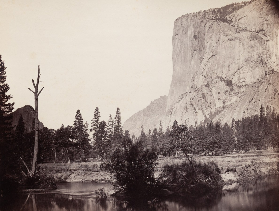 Ninteteenth century photograph of a river in the foreground with a sheer rock cliff face in the distance